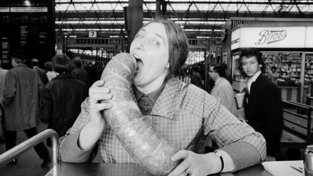 A woman poses with a large haggis in an old black and white photo