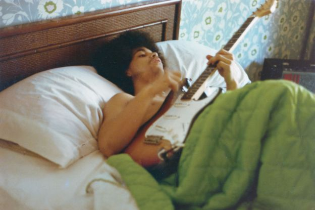 Prince plays a guitar in bed at his new home on France Avenue, April 1978