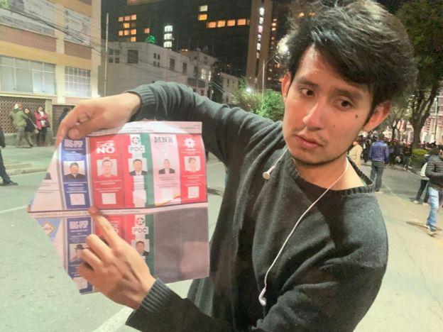 Un manifestante sostiene una boleta de votación