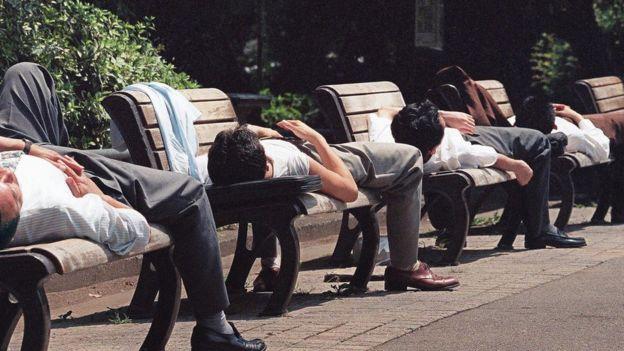 Homems pegam sol deitados em bancos no Japão, onde chegam a ocorrer mortes por trabalho excessivo