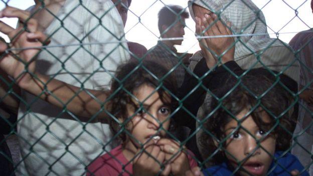 Asylum seekers arrive at Nauru off the Australian Navy troop carrier HMAS Manoora, 19 September 2001