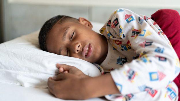 Menino dormindo em cama