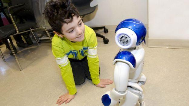 Niño juega con robot.
