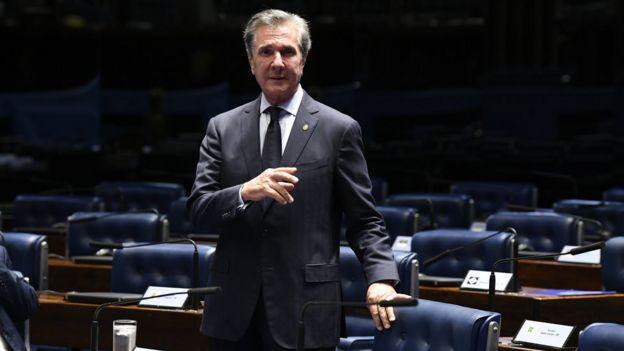 Collor em pé em meio a cadeiras dos parlamentares no Senado