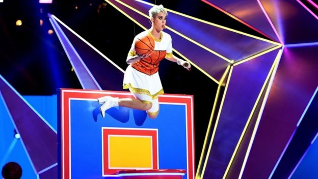 Katy Perry suspended over a basketball hoop mid performance