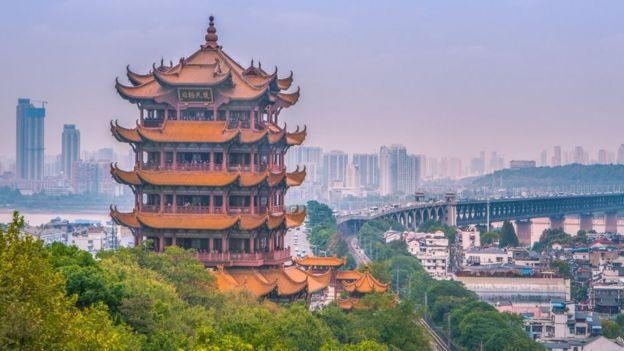 Construção antiga e típica em paisagem de Wuhan, de onde se vê também préditos e ponte