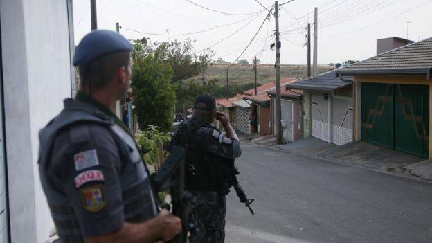 Dois policiais armados fazem patrulha de rua com casas