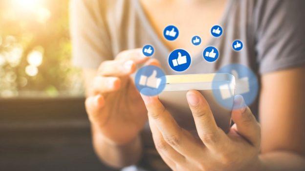 Mujer con un celular y los signos de me gusta de Facebook.