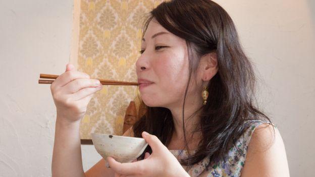 Jeune femme japonaise mangeant du riz