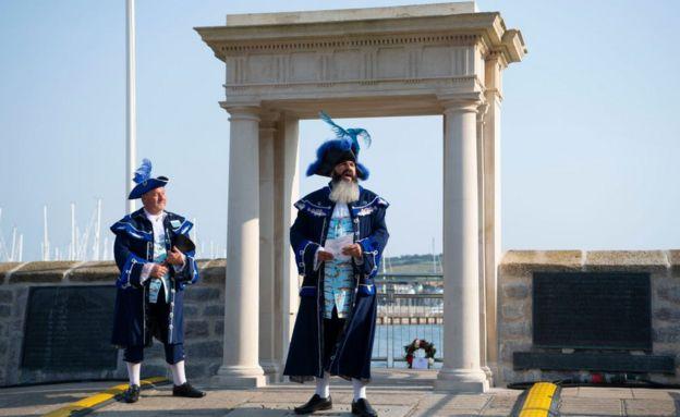 Hombres con trajes históricos en los escalones de Mayflower, el lugar donde se cree que los peregrinos abordaron el Mayflower hace 4 siglos en Plymouth, Inglaterra, en la celebración del aniversario.