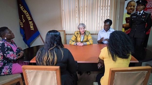 Theresa May speaks to two women at the Salvation Army headquarters in Lagos
