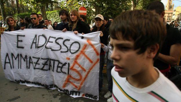 Los activistas anti-mafia llevan una pancarta con la leyenda