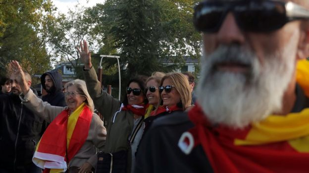 Franco supporters draped in Spanish flags wave outside the El Pardo cemetery where he will be re-buried