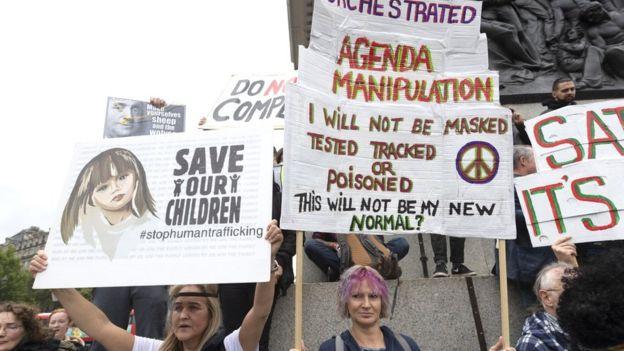 Slogan QAnon seperti 'Selamatkan anak-anak kita' terlihat berdampingan dengan poster konspirasi virus corona pada rapat umum hari Sabtu