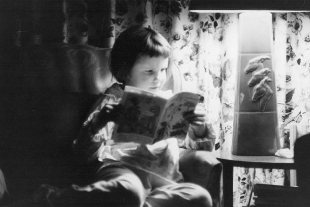 A black and white photograph shows Kathy reading a comic book or other sort of magazine