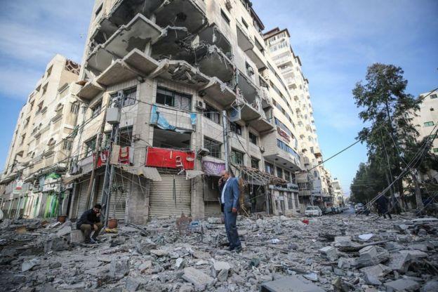 Dua orang warga Palestina memerik bangunan apartemennya yang rusak di Gaza City setelah serangan roket oleh militer Israel ke kawasn itu, Minggu, 5 Mei 2019. Mustafa Hassona/Anadolu Agency/Getty Images)