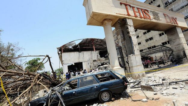 A car destroyed by the bomb sits outside the premises of ThisDay