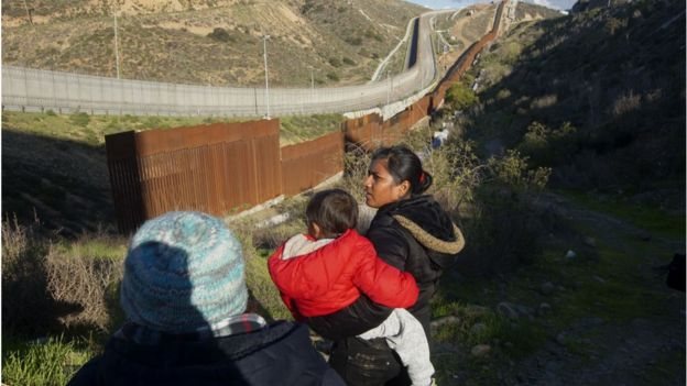 Honduran migrants walk toward the U.S.-Mexico border fence to cross over in Tijuana, Mexico