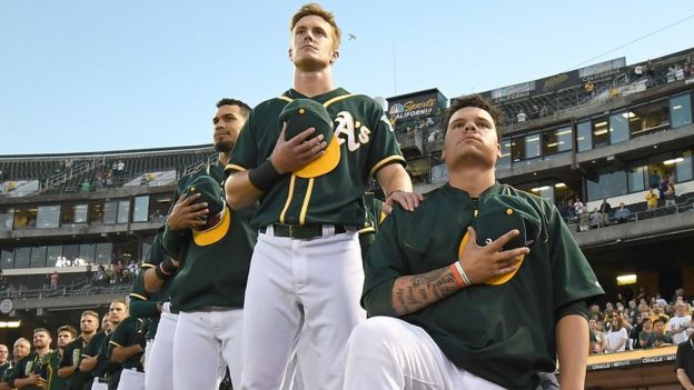 Baseball player Bruce Maxwell of the Oakland Athletics kneeling during the national anthem.