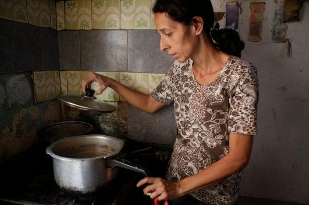 Mujer en una cocina con una cazuela.
