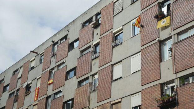 Banderas de España y de Cataluña cuelgan de ventanas en un conjunto residencial de Ciutat Meridiana.