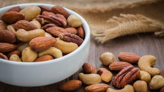 Pote com diversas frutas secas, como amêndoas e castanha de caju