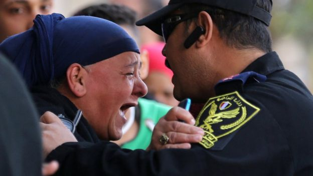 A relative of one of the blast victims screams at a police officer in front of St. Mark