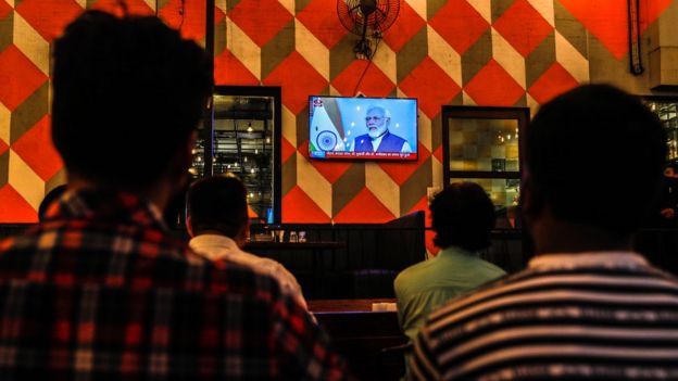 People watch a live address by Indian Prime Minister Narendra Modi after the government scrap Article 370, at a restaurant in Mumbai, India, 08 August 2019