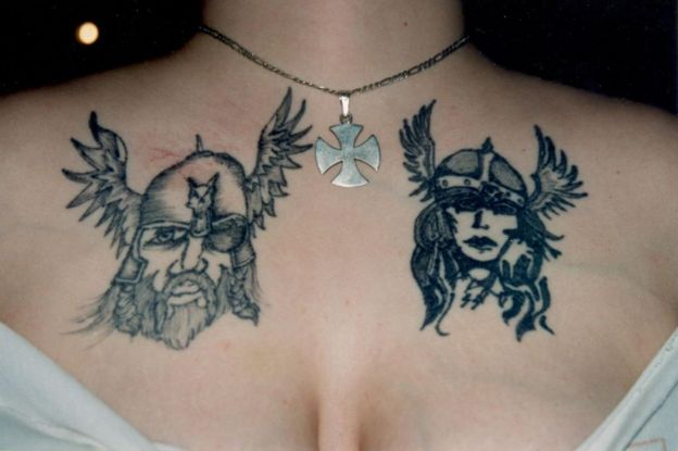 Angela's chest with two tattoos inspired by Norse mythology