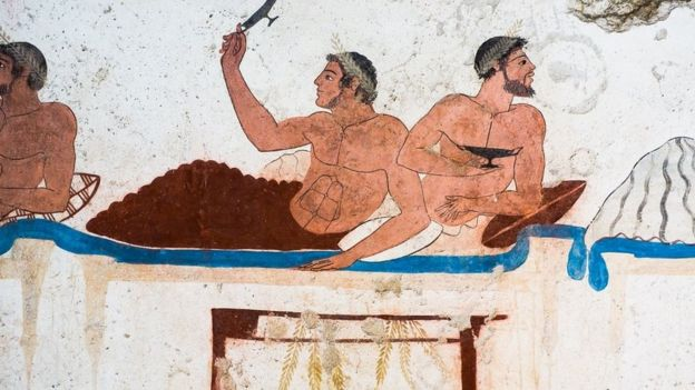 رسم لرجلين على سرير وأمامهما مأدبة طعام