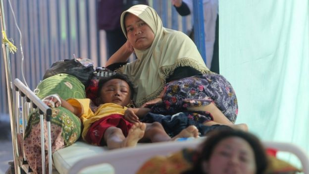 A mother accompanies her injured son at a hospital in Tanjung, northern Lombok, West Nusa Tenggara, Indonesia, 8 August 2018