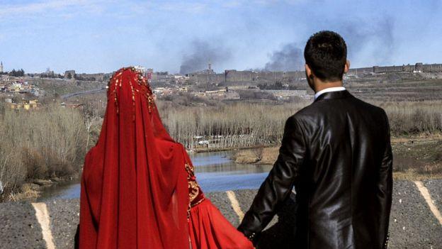 3 Şubat 2016'da çekilen bu fotoğrafta, düğün kıyafetleriyle poz veren bu çift, Diyarbakır'ın Sur ilçesinden çatışmalar nedeniyle yükselen dumana bakıyor