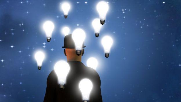 Hombre de espaldas con bombillos representando ideas