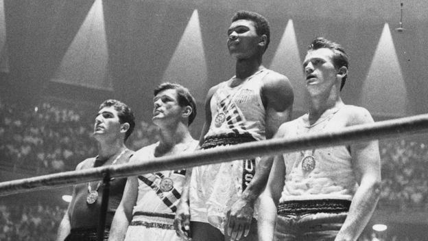 عکس کلی در حالیکه بالاتر از بقیه روی سکو ایستاده به یکی از تصاویر نمادین المپیک تبدیل شده است