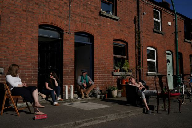 People chat while social distancing outside their homes