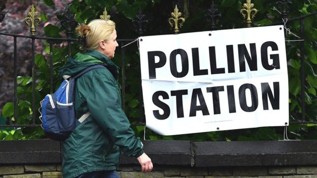 Woman walking past polling station sign