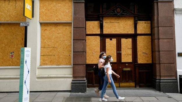 Women walking past boarded up London cafe