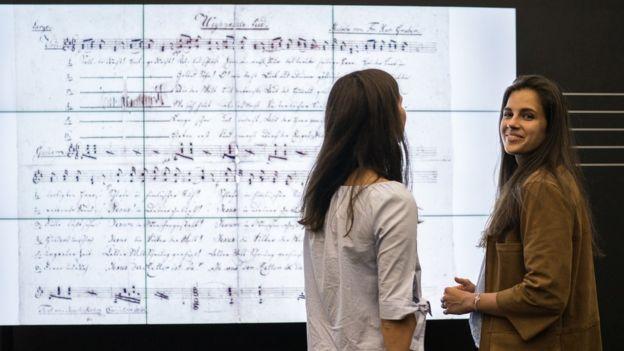 Jovens em frente à letra em exibição no museu de Salzburgo