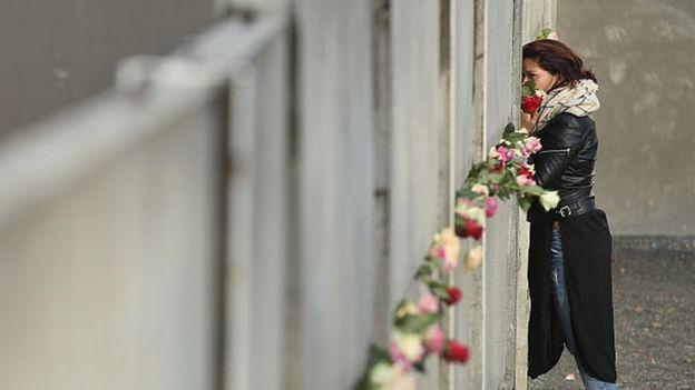 امرأة تقف بجانب جزء من سور برلين وقد وضعت به الورود