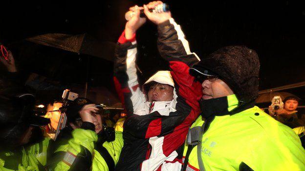 黃國昌在警方戒護下離開總統府前,高舉雙手。