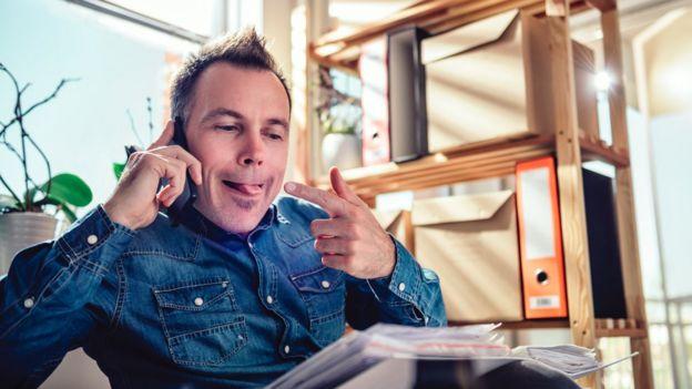 Un hombre habla por teléfono mientras se señala la lengua.