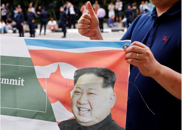 一名韩国男子在新加坡手持有金正恩的旗帜竖起大拇指支持峰会。