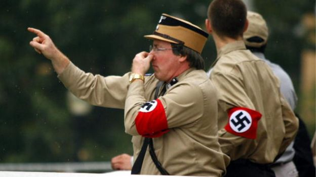 Homens vestindo uniforme com símbolos nazistas