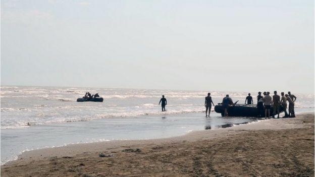 Надувные лодки и люди на берегу моря.