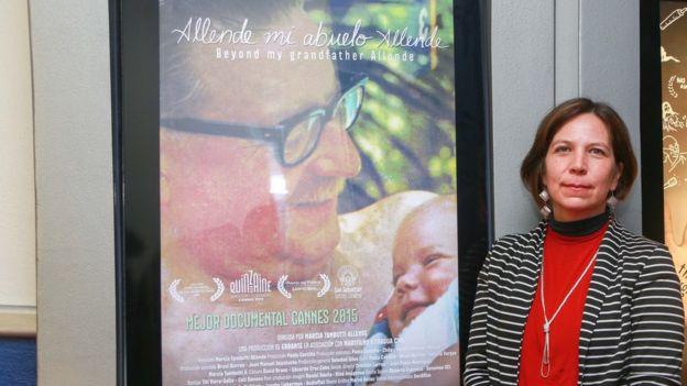 Marcia Tambutti frente al afiche de su documental sobre Allende
