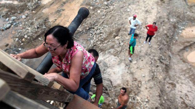 Una señora sube por una escalera improvisada con tablas de madera.