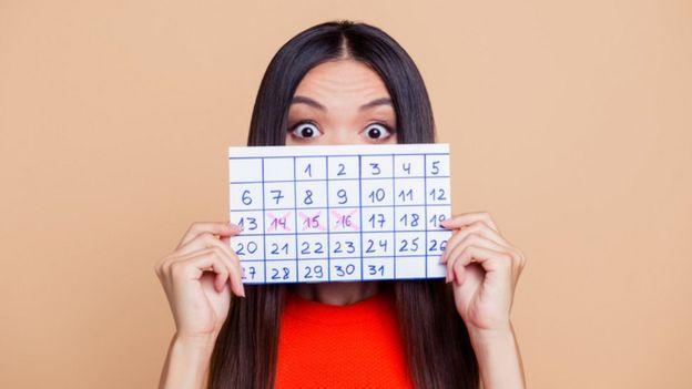 Mujer sostiene un calendario con sus días de menstruación.