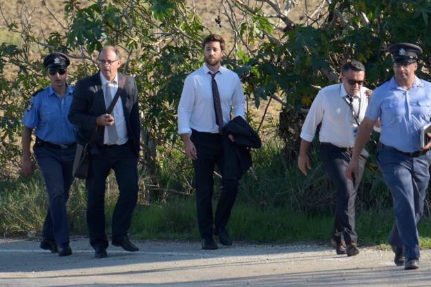 El hijo de la periodista asesinada Daphne Caruana Galizia, Matthew Caruana Galizia (en el centro, con camisa y corbata y el saco en la mano) y su esposo Peter Caruana Galizia (a su izquierda, con gafas y bolso), en la escena del crimen junto a la policía, en Bidnija, Malta, el 16 de octubre de 2017.