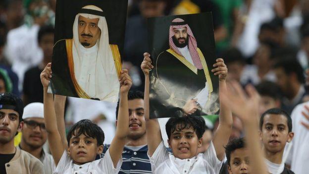 Seguidores de la selección de fútbol de Arabia Saudita sostienen fotos de la familia real durante un partido.