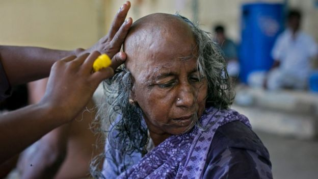 A Hindu devotee donating her hair at a temple in South India
